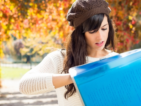 Young brunette student looking for papers in notebook on autumn background Stock Photo - 15616022