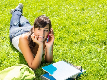 Beautiful young girl talking by mobile phone lying on green grass and smiling. photo