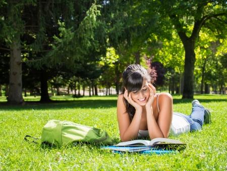 漂亮的黑发青少年学习外面。她微笑着在公园里读一本书。