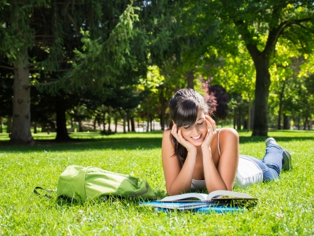 Pretty brunette teen studying outside. She is smiling while reading a book in a park.