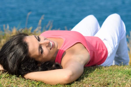 Young cheerful brunette woman lying down towards the blue sea, relaxing and enjoying Stock Photo - 15812326