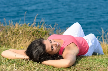 Young cheerful brunette woman lying down towards the blue sea, relaxing and enjoying Stock Photo - 15812328