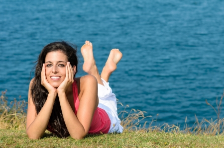 Beautiful young brunette looking at camera and smiling, lying down on grass with blue sea on background Stock Photo - 15812329