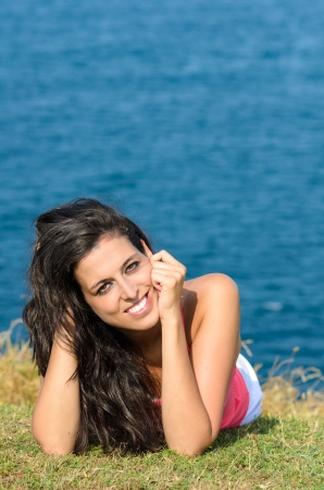 Beautiful young brunette looking at camera and smiling, lying down on grass with blue sea on background Stock Photo - 15812331