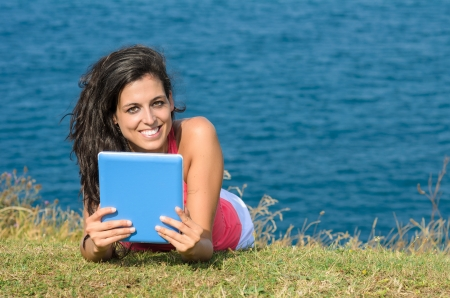 Young beautiful woman using tablet on vacations and smiling looking at camera. Blue sea on background. Stock Photo - 15812332