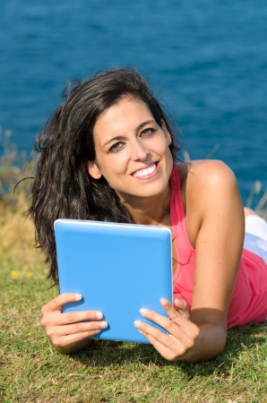 Young beautiful woman using tablet on vacations and smiling looking at camera. Blue sea on background. Stock Photo - 15812330