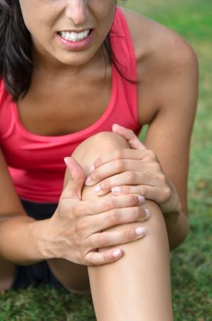 lesionado: Una mujer joven en el dolor a causa de una lesi�n en la rodilla. Ella agarra la rodilla con las manos con una expresi�n de sufrimiento.