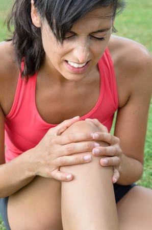 de rodillas: Una mujer joven en el dolor a causa de una lesión en la rodilla. Ella agarra la rodilla con las manos con una expresión de sufrimiento.