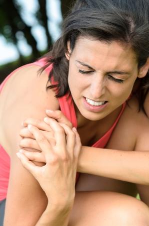 epaule douleur: Jeune femme attrapant son épaule avec une expression de douleur à cause d'une blessure musculaire. Banque d'images