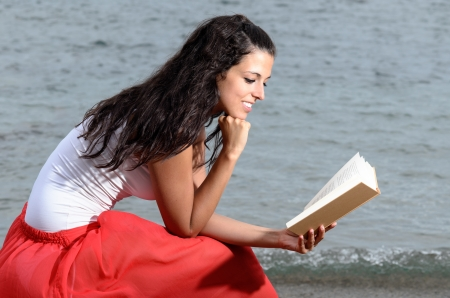 peacefulness: Brunette young woman reading a book, enjoying peacefulness and smiling happy on sea background in summer afternoon. Tranquility scene.