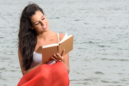 Brunette young woman reading a book and smiling happy on sea background in summer afternoon. photo