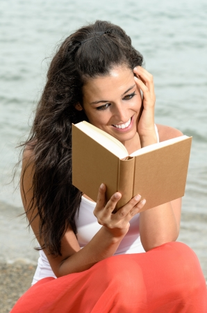 Brunette young woman reading a book and smiling happy on sea background in summer afternoon. She is touching her face with her hand with dreamy looking. photo