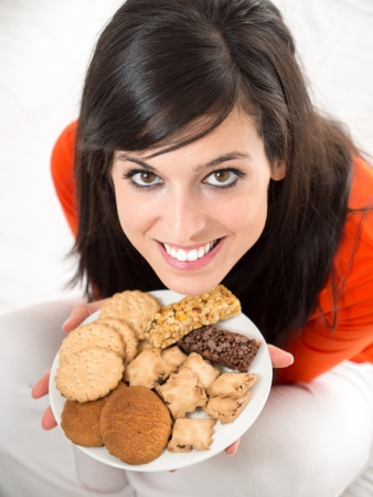 guilty pleasures: Cute brunette woman eating sweet cereal and chocolate biscuits in bed. Adorable and charming model, looking at camera and smiling.