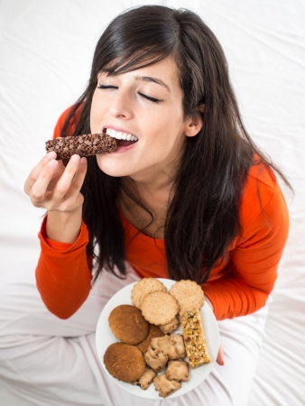 sweet tooth: Beautiful hispanic woman tasting a delicious chocolate bar sitting on a white bed indoors. Pleasure of biting a crunchy snack.