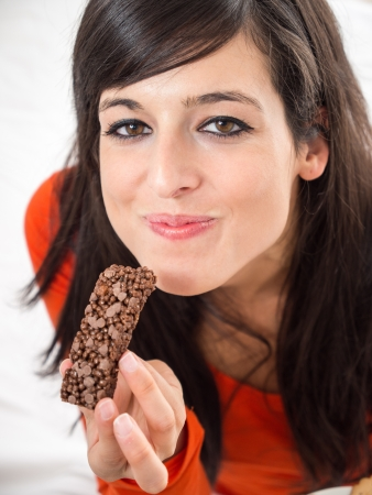 Beautiful young girl smiles with a mouthful while savoring a delicious and crunchy chocolate bar. Stock Photo - 16119953