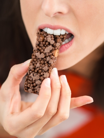 Detail of a woman hand and mouth eating a crunchy chocolate bar. White teeth and beautiful mouth photo