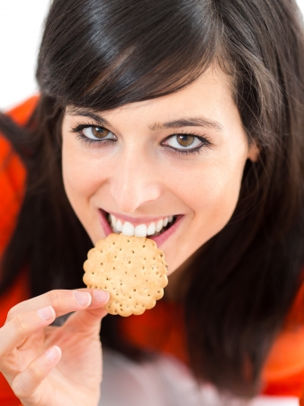 guilty pleasure: Woman smiling and biting a crunchy biscuits. Eating with funny looking face and eyes.
