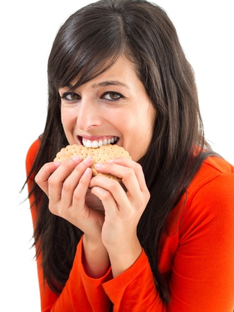 guilty pleasure: Funny woman smiling and biting many crunchy biscuits. she jokes getting a lot of crackers in the mouth. Stock Photo
