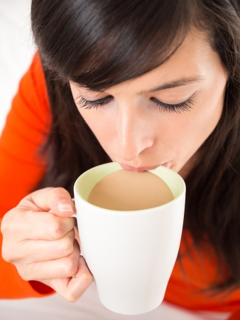 sipping: Close up of a young brunette woman sipping a cup of hot coffee