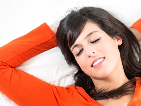 peacefully: Brunette woman sleeping peacefully in white bed. Happiness expression in her face.