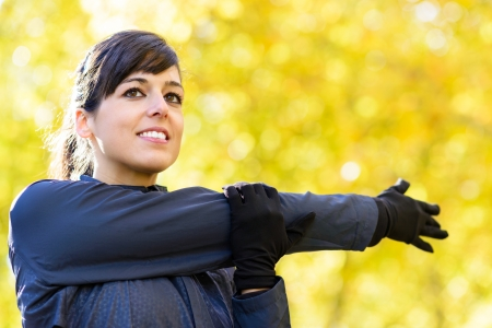 Beautiful brunette sport woman smiling and stretching shoulder and arm outdoor. Autumn blur golden leaves on background. photo