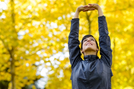 sportwoman: Beautiful sport fitness woman stretching with arms up on park outside. Autumn golden leaves and foliage on blur background. Stock Photo