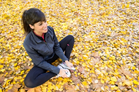 sportwoman: Beautiful sporty woman training and stretching legs sitting on autumn golden leaves outside.