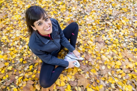 abductor: Beautiful sporty woman training and stretching legs sitting on autumn golden leaves outside.