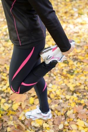 Femme dans leggins noirs debout sur un seul pied pour étirer la jambe. Automne feuilles d'or sur le fond.