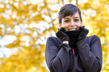 sportwoman: Beautiful sport woman with scarf feeling cold in fall. Autumn blur trees on background.