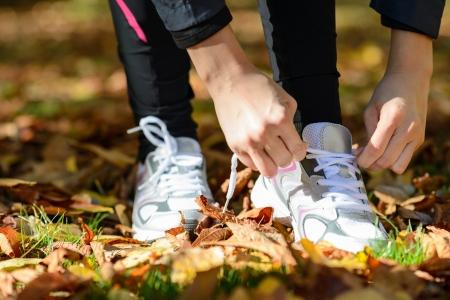 levantandose: Deporte detalle de las manos de la mujer tiying cordones de los zapatos. Mujer atleta preparándose para correr en el parque exterior.