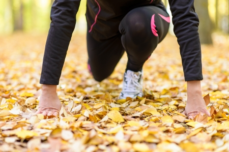 sportwoman: Sport woman in getting ready  for running pose with hands on ground and flexed knee. Autumn outside.