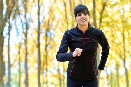 firmeza: Mujer atleta ejecuta fuera en un parque. Mujer alegre deporte hispano y caucásico ejercicio.
