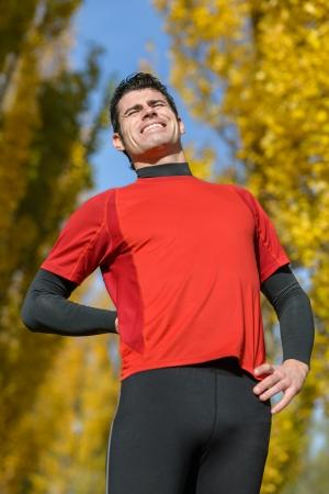 dolor de espalda: Atleta masculino que sufre de dolor de espalda severo. Cauc�sico deportista mostrando su dolor f�sico.