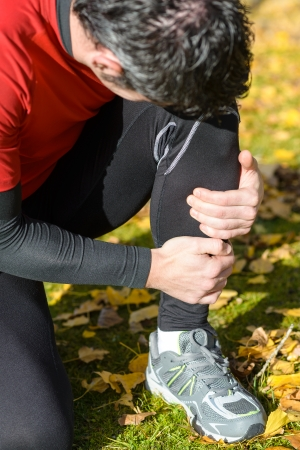 tibia: Male athlete suffering a tibia fracture. Grabbing his painful leg with two hands. Stock Photo