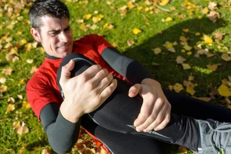 dolor de rodilla: Atleta masculino tendido en el suelo y sufrir una fractura de tibia. Agarrando su pierna dolorida con las dos manos.