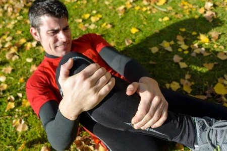 body wound: Male athlete lying on the ground and suffering a tibia fracture. Grabbing his painful leg with two hands. Stock Photo
