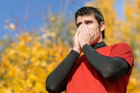 allerg�nes: Jeune athl�te toux et souffle avec un mouchoir. Caucasien mod�le hispanique m�le.