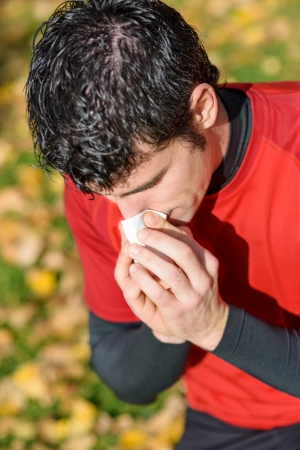 allergic reaction: Young athlete coughing and blowing with a tissue. Caucasian hispanic male model.