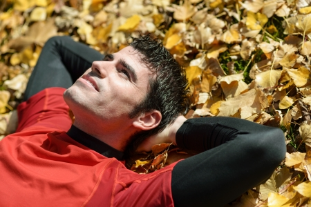 Deportista guapo descansando acostado en el suelo con las hojas de otoño de oro. Relajante y actitud el día soñando.