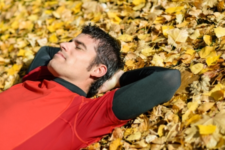 Handsome sportsman resting and sleeping lying down on ground with autumn golden leaves. Relaxing serene and peaceful attitude. photo