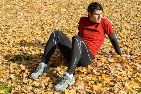 cansancio: Sentada guapos atletas en reposo sobre el suelo lleno de hojas de otoño de oro. Modelo Deportivo Hispano Cabello oscuro.