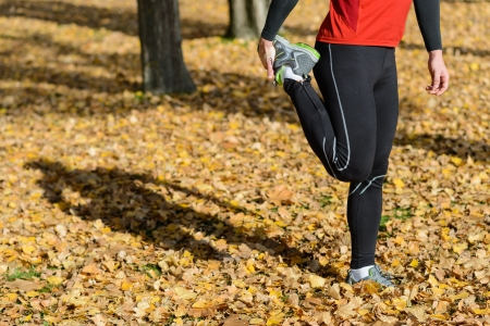 quadriceps: Unrecognizable male athlete stretching leg quadriceps outside. He projects shadow on foliage in ground.