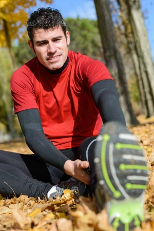 Cheerful handsome athlete stretching leg sitting on ground in autumn park. Hispanic sporty caucasian male model training. photo