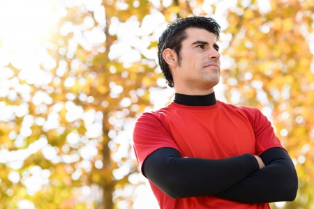 self confidence: Handsome sportsman idly with self confidence attitude. Outdoors scene in nature with blur trees on background. Hispanic male model. Stock Photo