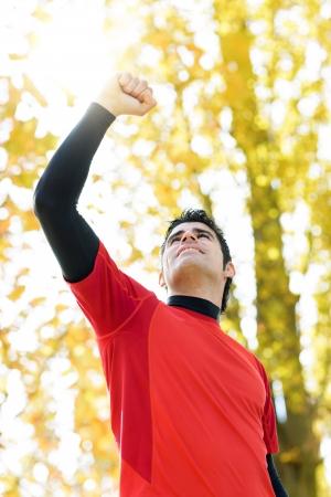 Deportista guapo celebrando la victoria levantando el brazo y el puño con el sol detrás. Outdoors escena en un parque con árboles y la naturaleza desenfoque en el fondo. Ganador hispano modelo masculino. Foto de archivo - 16599214