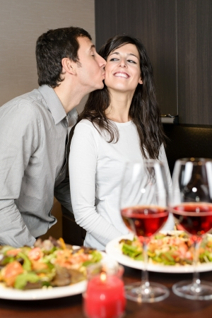 Romantic anniversary dinner. Young playful couple having fun during the celebration. Man kissing cheerful woman. photo
