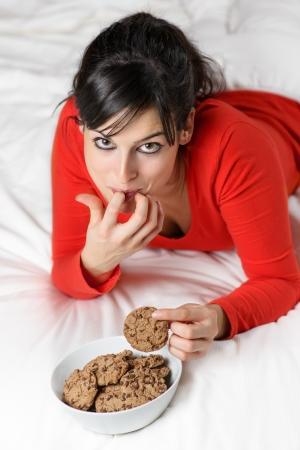 guilty pleasures: Young woman eating sweet cookies in bed. Caucasian brunette model enjoying delicious food.