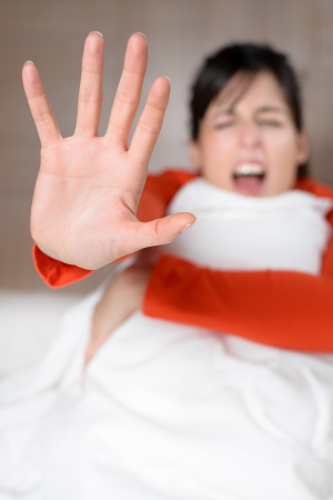 Woman screaming and showing hand for stopping abuses, noises or problems. Fear concept with scared brunette model in bed. photo