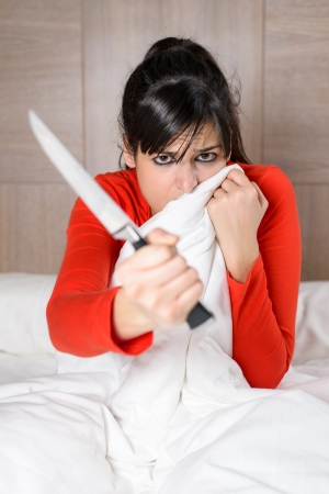 preoccupation: Frightened woman covering with the sheet on the bed and holding a knife in her hand. Brunette model looking scared and threatening in her room. Stock Photo